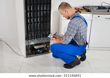Young Plumber Writing On Clipboard In Front Of Refrigerator Appliance In Kitchen Room