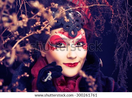 Young plump woman in creative image  in russian style  with artistic red and white visage  and with twigs - stock photo