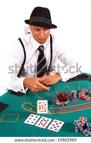 Young Poker Player Folding Young poker player is tossing his cards with a hat and stylish suit. Isolated over white background. - stock photo