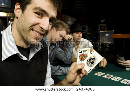 Young poker player holding winning hand in bar - stock photo