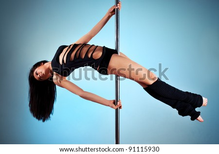 Young pole dance woman. On blue wall background. - stock photo