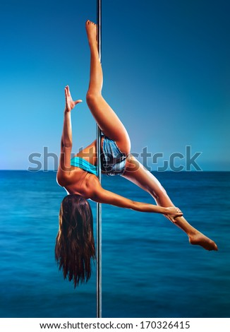 Young pole dance woman on sea background.