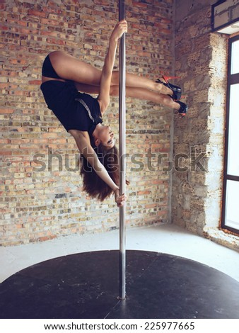 Young pole dancer woman trains on grunge interior with brick walls - stock photo