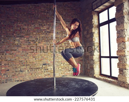 Young pole dancer woman wearing grey sports wear and colorful sneakers trains on grunge interior with brick walls - stock photo