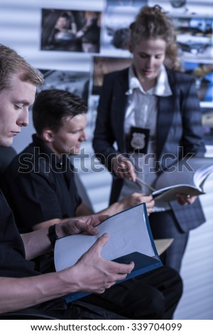 Young police officer is reading investigation files - stock photo