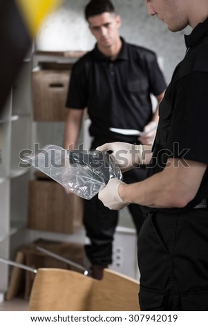 Young police officer preventing evidence of crime - stock photo