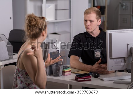 Young policeman is taking testimony from woman - stock photo