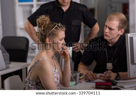 Young policeman questioning woman at police station - stock photo
