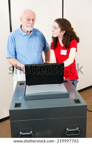 Young polling place volunteer helps a senior voter cast his ballot on new electronic equipment.   - stock photo