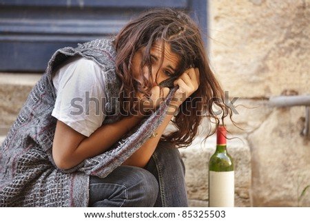 young poor girl drunk sitting in city street - stock photo