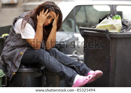 young poor girl very sad sitting on bin trash - stock photo