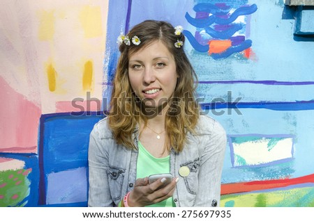 Young posing against a colorful backdrop holding smart phone