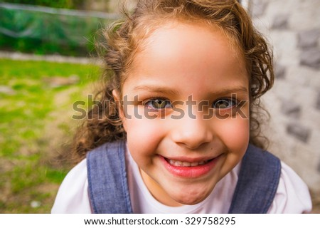 Young posing brunette girl closeup for camera and green background. - stock photo