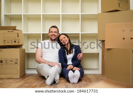 Young positive couple  among boxes in their new home - stock photo