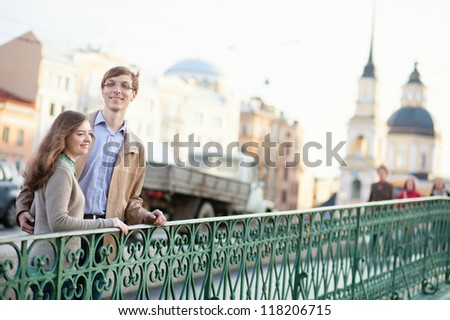 Young positive couple having a date outdoors - stock photo