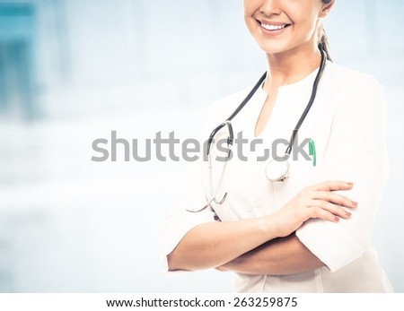 Young positive doctor woman in hospital hallway - stock photo