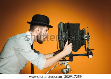 Young positive man in hat as photographer looking into the lens of  retro camera on an orange background - stock photo