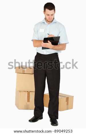 Young post employee with parcels taking notes on his clipboard against a white background - stock photo
