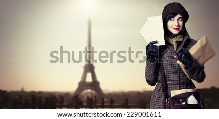 Young postman girl with mail. Photo with Eiffel tower on background. - stock photo