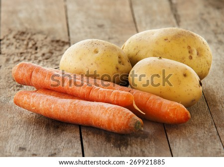 young potatoes and carrots on wooden background - stock photo