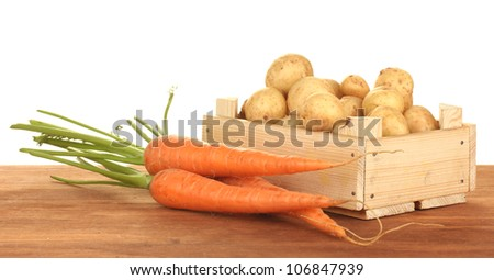 young potatoes in a wooden box with carrots on a table on white background close-up
