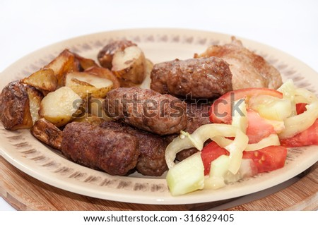 Young potatoes kebabs fried pork tomato salad paprika.