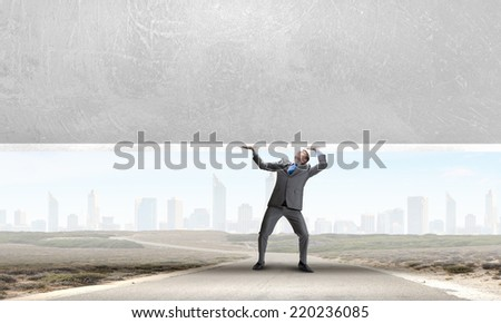 Young powerful businessman lifting brick wall above head - stock photo