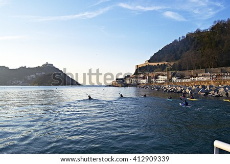 Young practicing canoeing at sunset in San Sebastian, Spain - stock photo