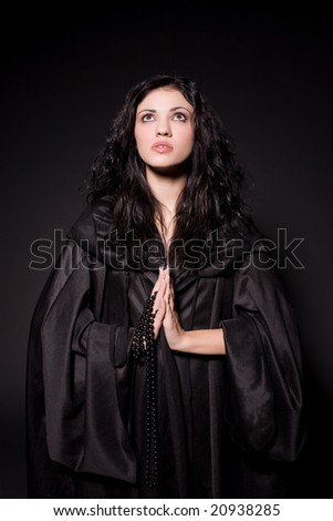 Young praying girl in nun outfit over black background - stock photo