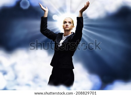 Young praying saint businesswoman with halo above head - stock photo
