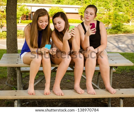 Young pre-teen girls texting while hanging out in front of their school