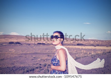 young pregnant Asian woman with a scarf to developing holding on to her belly on the background of desert nature. - stock photo