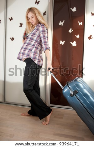 Young pregnant blonde with suitcase ready to travel - stock photo