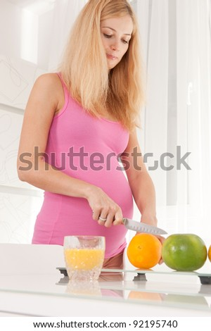Young pregnant blonde woman cutting orange in kitchen