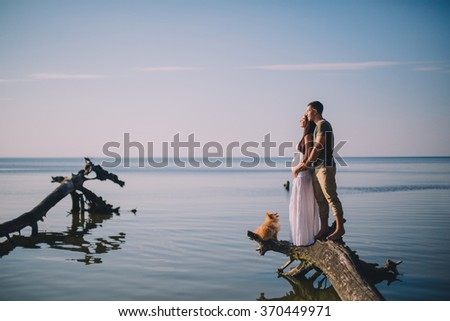 Young pregnant couple in love on summer sunny evening, with dog - stock photo