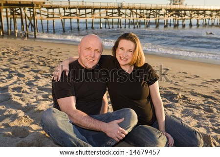 Young Pregnant Couple on the Beach with Pier in Background at Sunset - stock photo