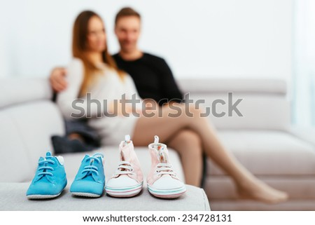 Young pregnant couple sitting on a sofa and looking at baby boots - stock photo