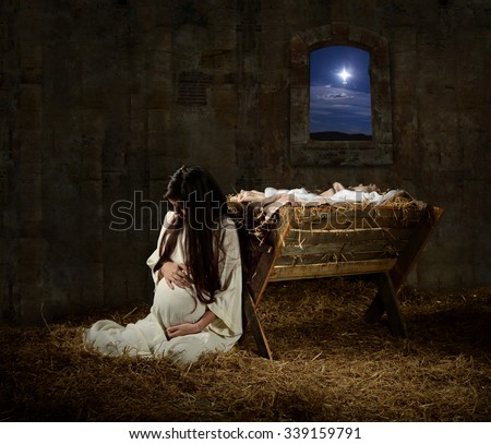 Young pregnant Mary praying leaning on manger on Christmas Eve - stock photo