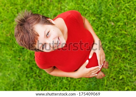 Young pregnant mom expecting a baby, standing over green grass