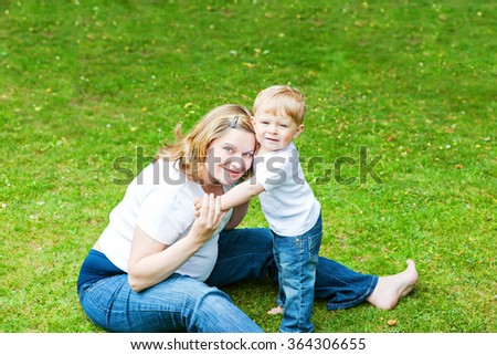 Young pregnant woman and adorable little toddler son in summer garden. Mother and child having fun together. Happy family of two on warm day. Small difference between siblings concept. - stock photo