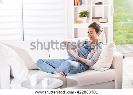 young pregnant woman at home using a tablet, she is lying on a white couch