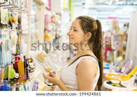 Young pregnant woman choosing baby stuff at baby shop store - stock photo