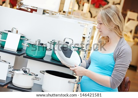 Young pregnant woman choosing kitchen pot in home appliance shopping mall supermarket - stock photo