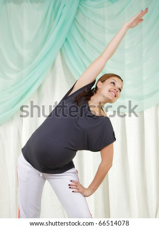 Young pregnant woman doing exercises