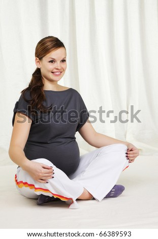 Young pregnant woman doing yoga exercises on sitting on the floor