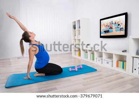 Young Pregnant Woman Exercising In Front Of Television At Home - stock photo