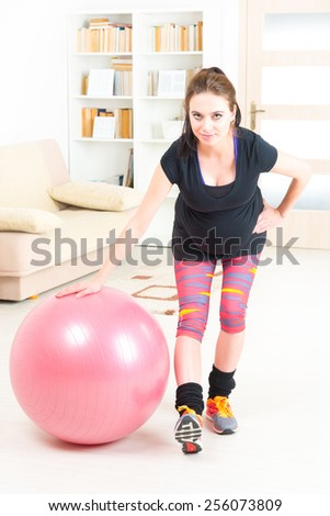 Young pregnant woman exercising with gym ball at home - stock photo
