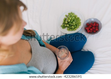Young pregnant woman holding a glass of drinking water which is good for her health. two plates of grapes and raspberries standing beside her - stock photo