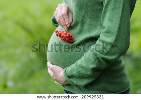 Young pregnant woman holding ashberry in her hands  - stock photo