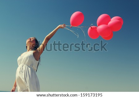 Young pregnant woman holding red balloons. Photo in old color image style. - stock photo